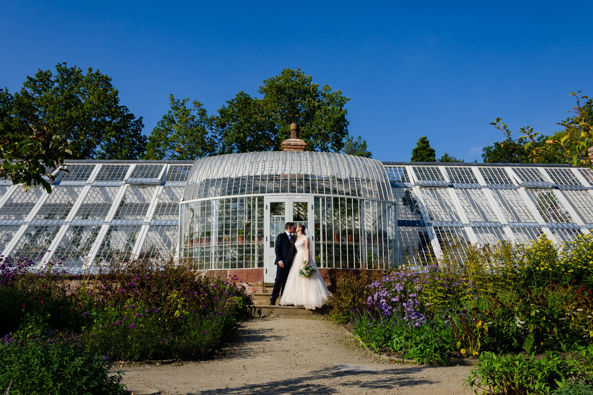 Quarry bank mill Bride & Groom kiss in front of glass house in sunshine with blue sky