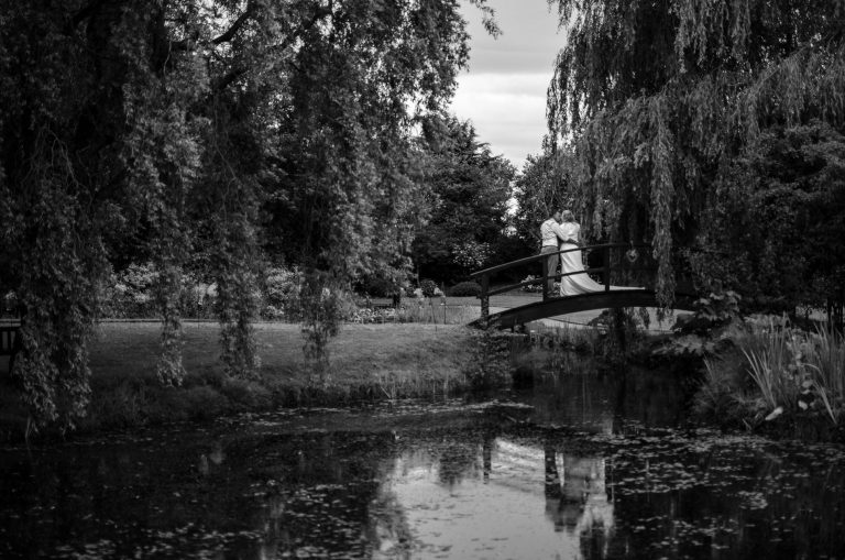 Black and white image of couple on bridge with reflection at Manly Mere, Weepin Willows in the background