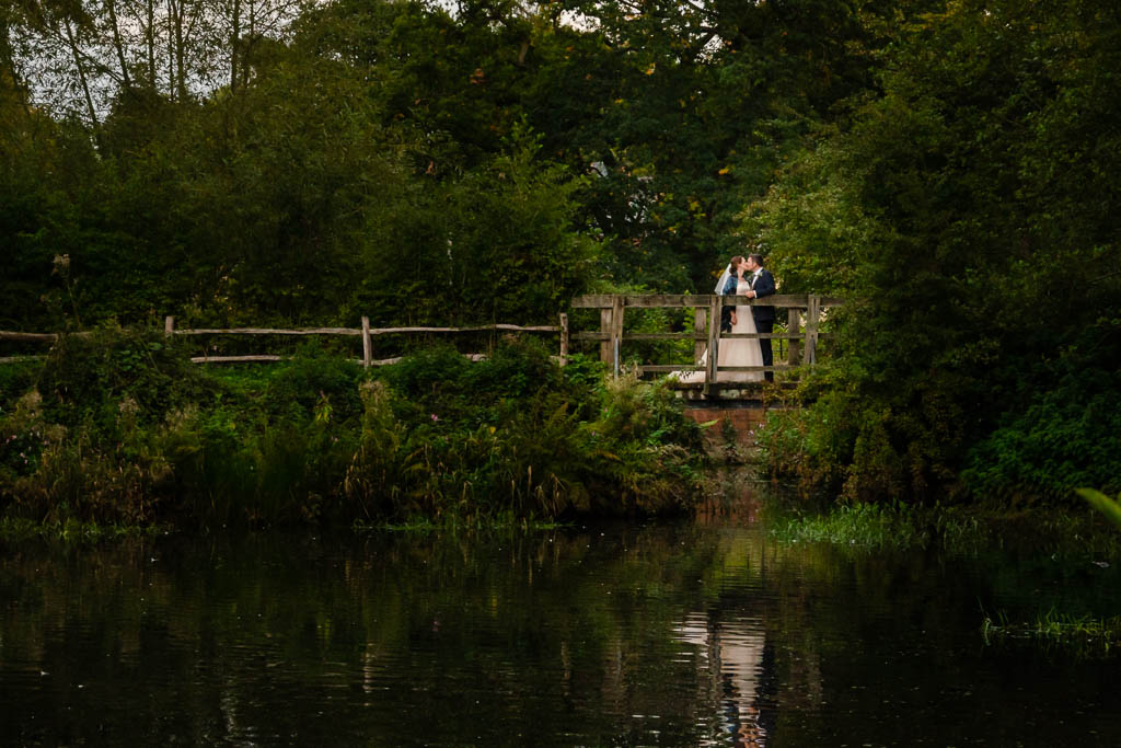 Beautiful relaxed portrait, Bride & Groom in reflected in Mill Pond at QUarry Bank Mill