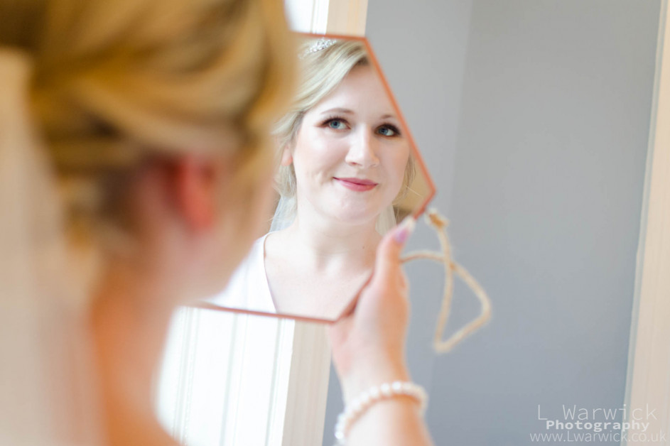 Bride checks her make up in a hand held mirror