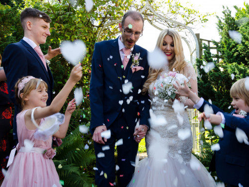 Newly weds showered in confetti by their family