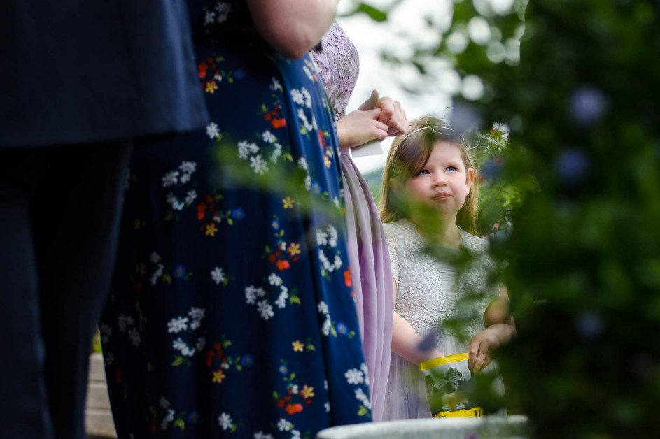 Cute little bridesmaid enjoying a packet of crisps surrounded by adults